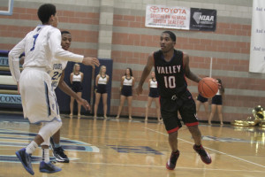 Valley senior guard Cam Burton (10) drives against a pair of Foothill Falcons.